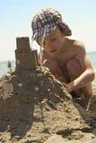 做沙堡的海滩的年轻男孩 免版税图库摄影