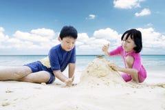 做沙子城堡的两个孩子在海滩 免版税库存图片