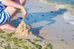 做沙子城堡的女孩在海滩 库存照片