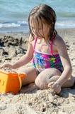 做沙子城堡的女孩在海滩 免版税库存图片