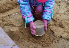 做沙子饼的小女孩 免版税图库摄影