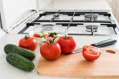 做沙拉用蕃茄和黄瓜在厨房里 免版税库存图片