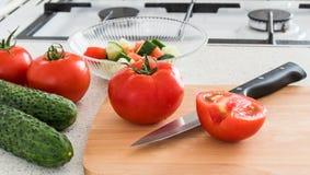 做沙拉用蕃茄和黄瓜在厨房里 库存照片