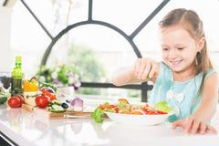 做沙拉的逗人喜爱的小女孩 儿童烹调 健康的食物 免版税库存图片