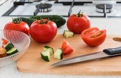 做沙拉whis蕃茄和黄瓜在厨房里 免版税库存照片