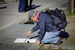 做油漆的老人在街道 免版税图库摄影