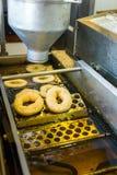 做油炸圈饼的机器 图库摄影