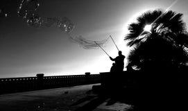 做泡影的人在热带日落 图库摄影