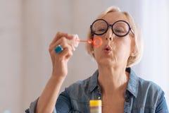 做泡影的愉快的老妇人 库存照片