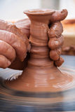 做泥罐的手 免版税库存照片