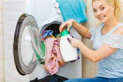 做洗衣店的女孩使用液体洗涤剂 免版税图库摄影