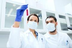 做测试或研究的年轻科学家对实验室 免版税库存照片