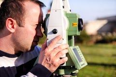 做测量在庭院里,总驻地的测量员工作者 图库摄影