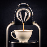 做浓咖啡杯子的咖啡机器 库存照片