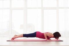 做海豚板条姿势的瑜伽席子的健身妇女 库存照片