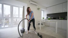 做清洗的真空的快乐的主妇女性和有乐趣跳舞并且在屋子里在家唱歌 股票视频