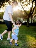 做滑稽的面孔和表示的愉快的男孩,当走与他的祖母时 图库摄影