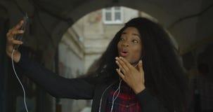 做滑稽的面孔的可爱的相当非洲女孩的侧视图,当采取selfies通过室外时的手机 股票视频