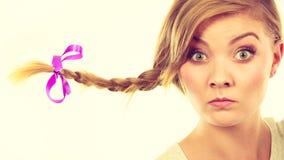 做滑稽的面孔的辫子头发的十几岁的女孩 免版税库存照片