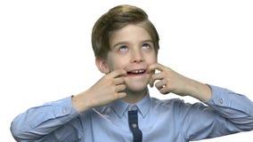 做滑稽的面孔鬼脸的青春期前的男孩 影视素材