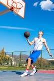 做灌篮的年轻篮球街道球员 图库摄影