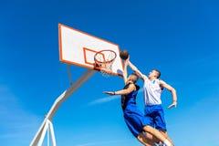 做灌篮的年轻篮球街道球员 免版税库存图片