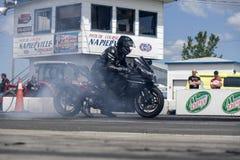 做烟的摩托车驾驶员显示在轨道 库存图片