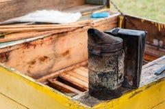 做烟的Beekeeper's工具在被打开的黄色蜂箱 免版税图库摄影
