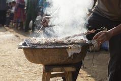 做烤肉用传统方式的亚裔人 库存照片
