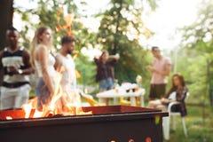 做烤肉的小组朋友在后院 关于好和正面心情的概念以朋友 免版税库存图片