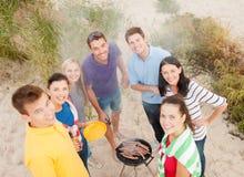 做烤肉的小组朋友在海滩 库存图片