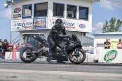 做烧坏的摩托车驾驶员在轨道 免版税库存图片