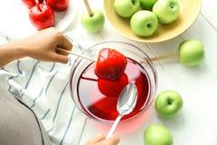做焦糖苹果的少妇 免版税库存照片