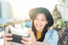 做照片在度假-年轻时髦亚裔女孩的愉快的中国influencer妇女采取室外的selfie 免版税库存照片