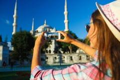 做照片由智能手机在蓝色清真寺附近, Istan的女孩 免版税库存图片