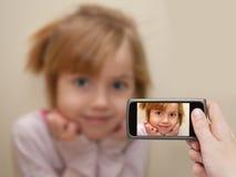 做照片的人的手有移动电话的一个小女孩。 免版税库存图片