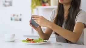 做照片的女孩菜沙拉在吃前,食物博客作者,烹饪技巧 股票视频