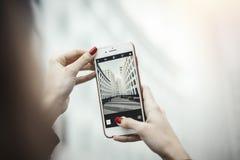 做照片的年轻可爱的女孩摩天大楼由手机 库存图片