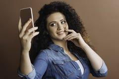 做照片的快乐的俏丽的女孩在她的电话 图库摄影