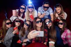 做照片的滑稽的小组学生在智能手机 库存图片