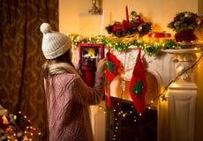 做照片的逗人喜爱的女孩装饰的圣诞节壁炉在数字 库存图片