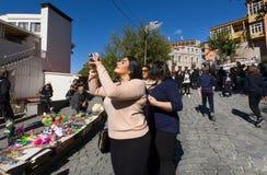 做照片的逗人喜爱的妇女在老城市街道  免版税库存图片
