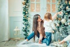 做父母和获得乐趣和一起使用在圣诞树附近的两个孩子 免版税库存图片