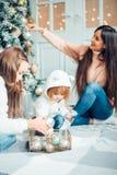 做父母和获得乐趣和一起使用在圣诞树附近的两个孩子 库存照片