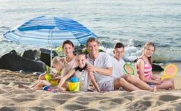 做父母孩子在阳伞下 免版税库存图片