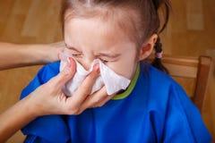 做父母帮助女孩的手吹她的鼻子 免版税库存照片