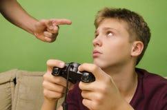 做父母教育他的孩子不打电子游戏 免版税库存图片