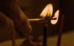 做父母点燃在蛋糕的` s手一个蜡烛 免版税库存图片
