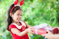 做父母给圣诞节礼物逗人喜爱的亚裔儿童女孩 库存图片