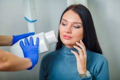 做牙齿治疗牙耐心女孩的牙医医生在牙齿办公室 免版税图库摄影